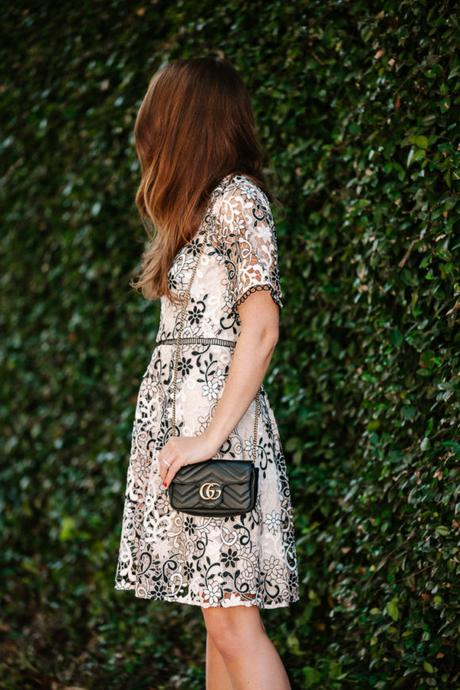 Amy Havins wears a blush and black lace dress.