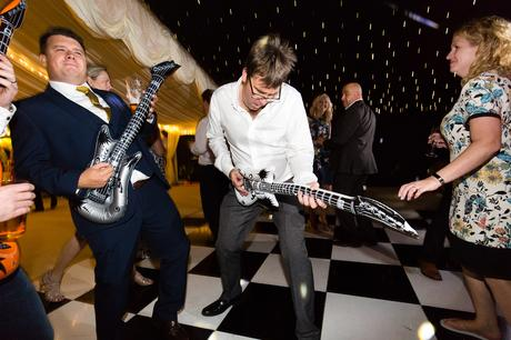 Guest playing blow up guitar at wedding