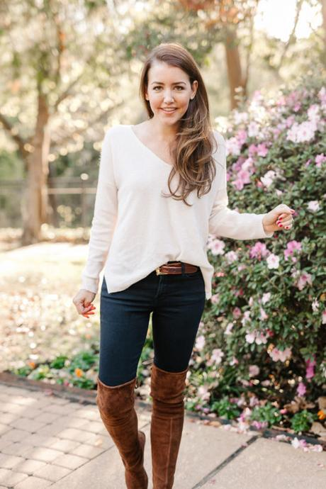 Amy Havins wears brown boots and a white sweater.