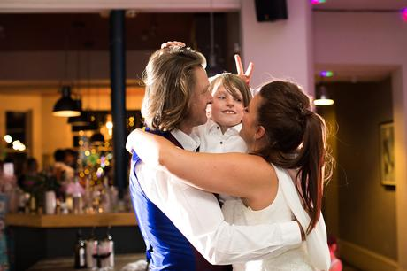 Family first dance with bride making bunny ears behind son