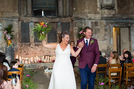 Bride and groom cheer as they walk up the aisle at quirky & fun wedding in London Asylum