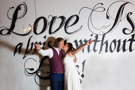 Bride and groom hold up sparklers at London wedding in front of graffiti
