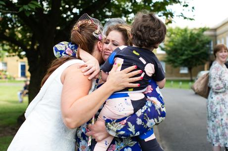 Candid photo of bride hugging guests at asylum wedding in London
