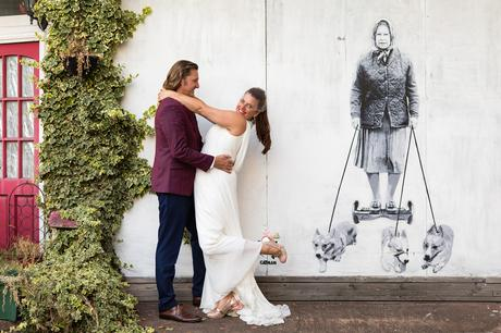 Bride and groom take quirky and fun photo in front of Banksy graffiti of queen and corgis in London