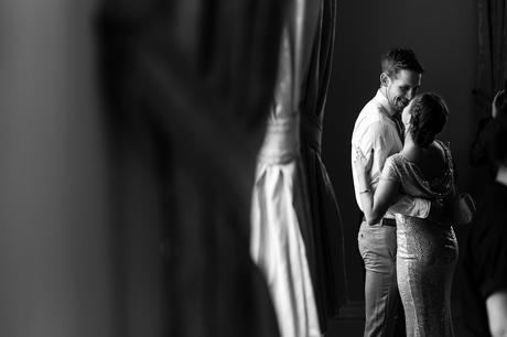 A couple sneak a kiss by the window at a Victoria Hall wedding