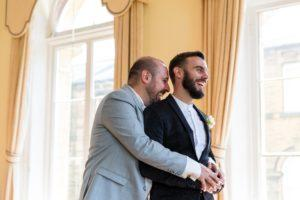 A fun Yorkshire Wedding grooms cuddling at same sex wedding