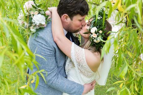 Boho bride & groom kiss under willow tree Villa Farm Weddings