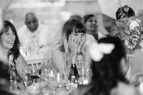 Guest laughs and covers face during speeches