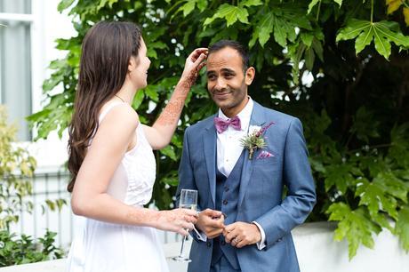 St. Stephens Hampstead Wedding bride picks confetti out of groom's hair