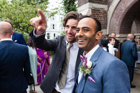 Candid wedding photo of man pointint
