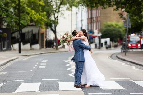 Bride and groom kiss at pedestrian crossing