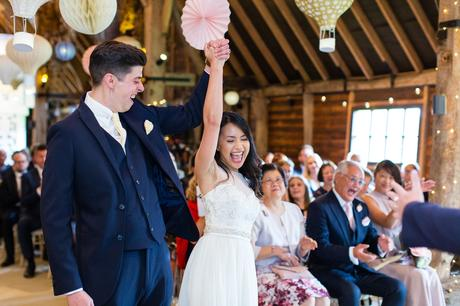 Giant cheer at the end of the ceremony with bride and groom holding hands in the air