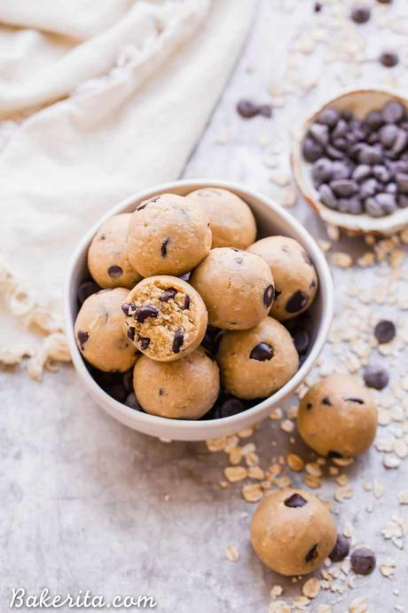 Oatmeal Chocolate Chip Cookie Dough Bites: Gluten Free & Vegan. Stacked in a bowl with oats and chocolate chips.