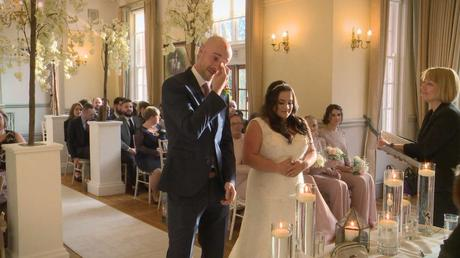 the groom uses a tissue to wipe away his tears after seeing his bride walk down the aisle on the wedding video for their Nunsmere Hall winter wedding