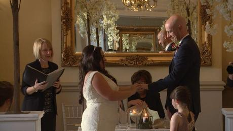 The bride laughs as she squeezes the wedding ring on to her groom on their wedding video