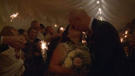the bride and groom kiss in the marquee walkway surrounded by guests and sparklers at Nunsmere hall in Cheshire