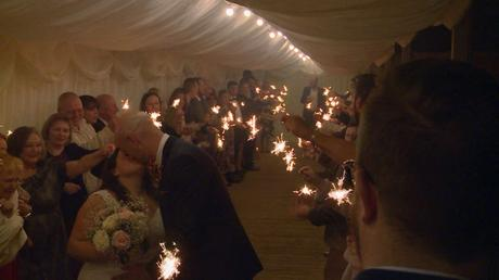 a bride and groom kiss as guests wave sparklers around and cheer for the video at Nunsmere hall