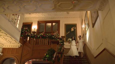 The bride walks down the grand oak staircase with her Mum. It's decorated with christmas garlands at Nunsmere Hall