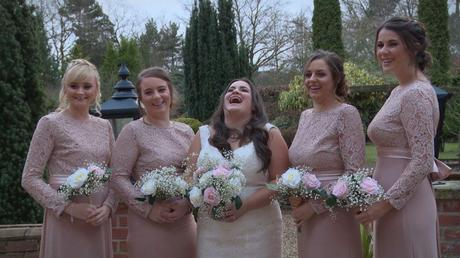 The bride and bridesmaids laugh out loud with their wedding videographer as they have formal photos taken outside nunsmere hall wearing blush pink and holding bouquets