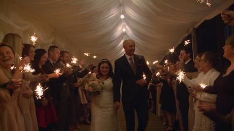 the bride and groom walk through a tunnel of guests waving sparklers during the evening reception at Nunsmere Hall