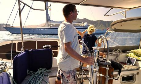 Jamie at the helm sailing by yacht M5