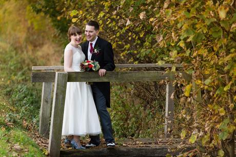 Bride in groom on bridge in autumn wedding Sandburn Hall Wedding Photography