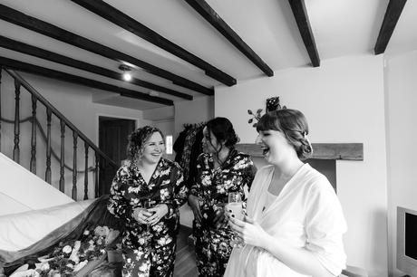 Bride laughing with bridesmaids in documentary wedding photograph