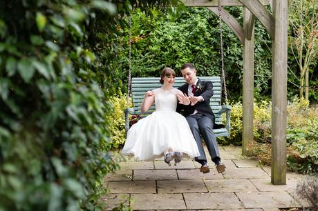 Bride and gorom on swing looking at rings