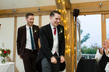 Sandburn Hall Wedding Photography groom walking away in handcuffs funny speech moment