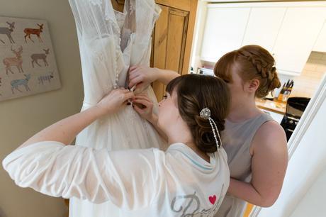 Yorkshire Wedding Photography Bride and sister unbuttoning wedding dress