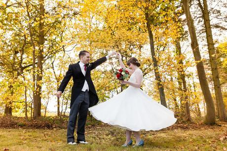 Groom twirls bride in yellow leaves Sandburn Hall Wedding Photography