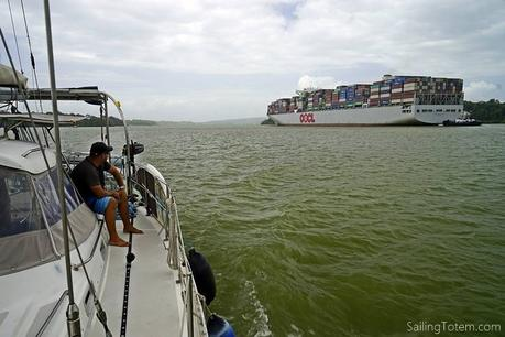 Sailboat passing OOCL cargo ship in the Panama Canal