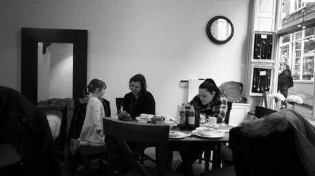 a grandma, aunt and niece sit around a cafe table after their lunch talking to a newborn baby in Lincoln