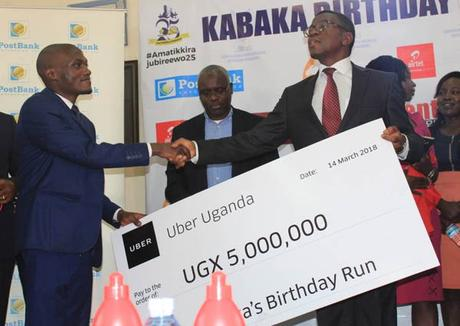 Aaron Tindie, country manager for Uber Uganda, hands a check to the Katikkiro of Buganda, Peter Mayiga