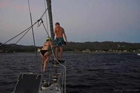 Kids swim from the bow of the boat