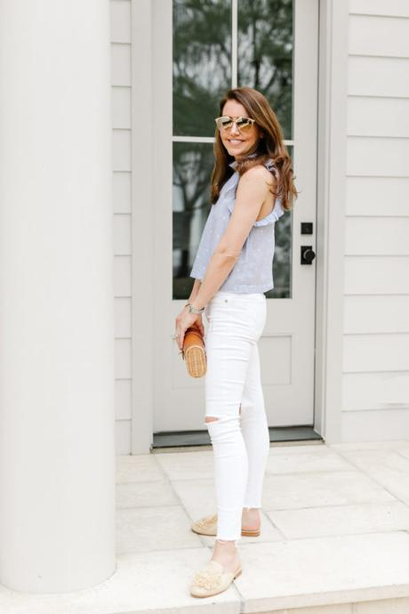 Amy Havins wears white jeans and a sleeveless ruffle blouse.