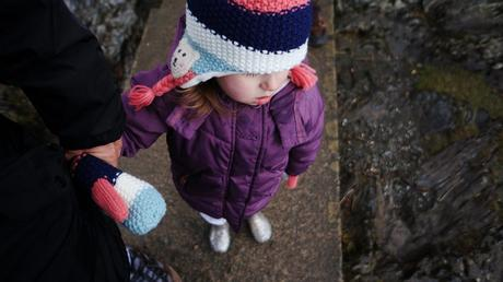 3 year old girl stands waiting for a boat at derwent water in her warm purple coat and matching polar bear hat and gloves
