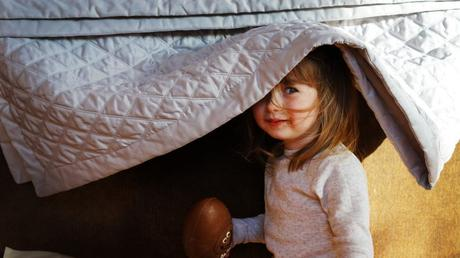 a little toddler girl smiles as she tried to hide herself and her easter egg under a silver throw hanging over a sofa as her Mum takes a photo in their holiday house in Penrith