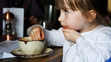 a little girl attempts to catch hot chocolate dripping down her chin as she enjoys a hot drink after a long cold walk in the lake district