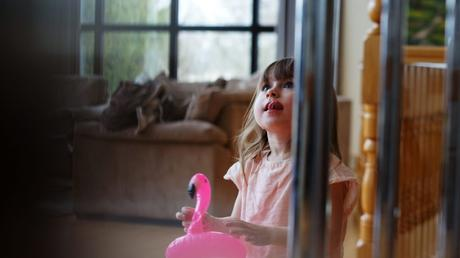 little girl holds a small inflatable pink flamingo in her hand as she looks up past the camera with a little smile