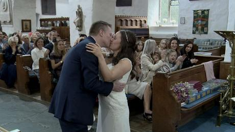 the bride and groom finally enjoy a kiss as the priest says you may kiss the bride as their family and friends applaud