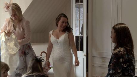 A bride shyly smiles at her best friend as she stands in her wedding dress waiting to leave for the ceremony. it looks like they're fighting back the happy tears