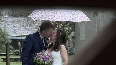 a bride and groom enjoy a kiss under a white and pink flowery umbrella. the video camera is looking through the old wooden church gate at St Oswalds church in the lake district