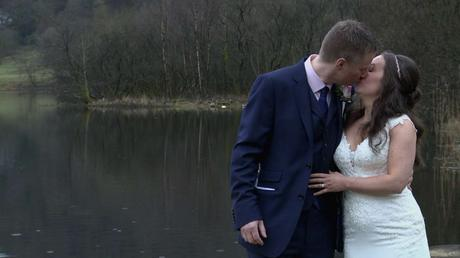 a bride and groom stand in the rain in front of Grasmere lake having a kiss for the wedding photographer