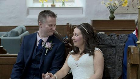the bride and groom look at each other with a smile as they sit during their wedding ceremony in the lake district