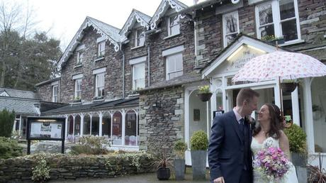 a bride and groom pose fro the wedding video under a pink and white flowery umbrella in front of the gray stone building that is The Wordsworth Hotel in Grasemere