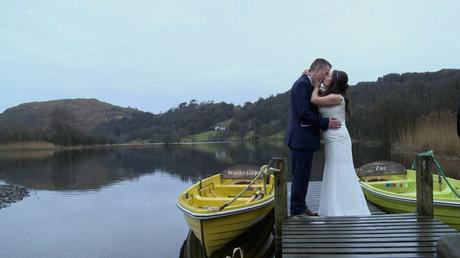 a bride and groom stand on a jetty by the side of Grasmere lake after their wedding in the lake district having a little kiss in the rain. A bight yellow and green rowing boat brighten up the gloomy scene