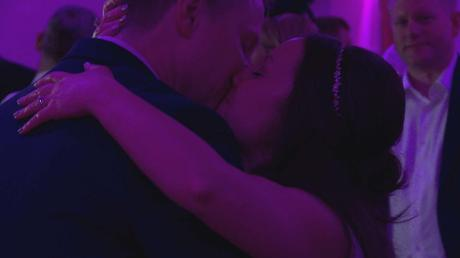 the bride and groom enjoy a kiss on the dance floor under pink lights for their wedding first dance at the wordsworth hotel