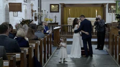 a flower girl stands in the middle of the aisle watching everyone clapping for her Mum and Dad getting married