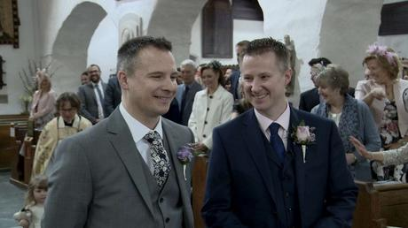 a groom and best man share a laugh standing at the front of St Oswalds church waiting for the bride to arrive